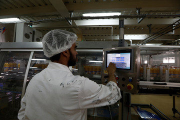 An employee monitors production at the Rouiba drinks factory on the outskirts of Algiers