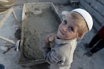 A young boy takes part in the construction of a structure on the West Bank Jewish settlement near Hebron