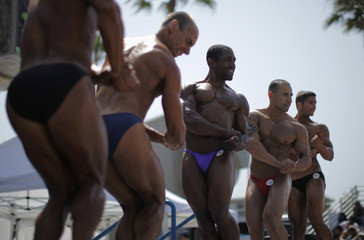 Men compete in the Muscle Beach Independence Day bodybuilding contest on Venice Beach in Los Angeles, California