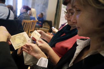 People learn the security features of euro banknotes during a workshop in Salacgriva