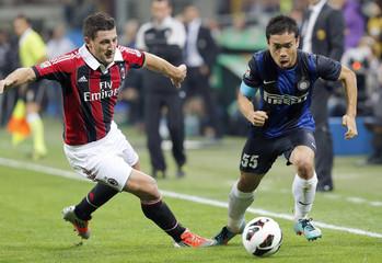 Inter Milan's Nagatomo is challenged by AC Milan's Bonera during their Italian Serie A soccer match in Milan