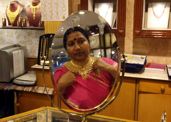A woman is reflected in a mirror as she tries on a necklace at a jewellery showroom in Kolkata