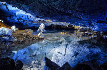 Slope of the mountain with the reflection in the water inside a fantastic cave. Kungur In The Urals