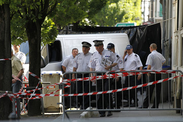 French police stand near a truck and black plastic sheet outside the house where a human body part was found in Nantes