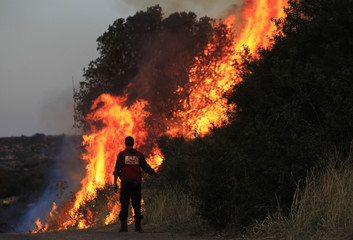 A fire-fighter works near a wildfire outside Moshav Lachish in southern Israel