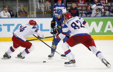 Russia's Kutuzov and Medvedev block Sweden's Nyquist during their men's ice hockey World Championship semi-final game at Minsk Arena in Minsk