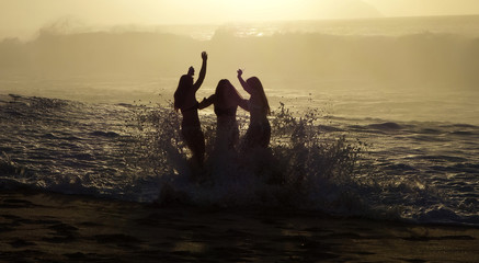 Girls get caught in the rough surf while taking pictures at Sunset Beach on Oahu's North Shore