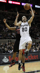San Antonio Spurs Manu Ginobili goes to the basket against Toronto Raptors DeMar DeRozan during the first half of their NBA basketball game in San Antonio