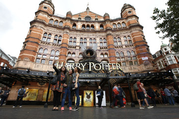 People take a selfie picture outside The Palace Theatre where the Harry Potter and The Cursed Child play is being staged, in London