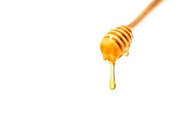 honey on wooden dipper white background