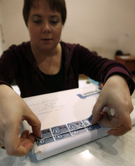 An employee places postage stamps on a package at a post office in the capital Tbilisi