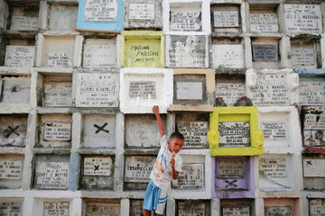 A boy, hanging from apartment-style tomb, eats ice-cream as people visit graves of their loved ones ahead of the commemoration of All Saints day at Navotas Public cemetery in Manila
