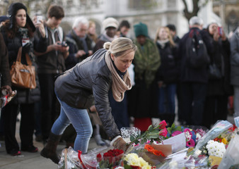A woman lays roses at the foot of a statue of former South African President Nelson Mandela in Parliament Square in central  London