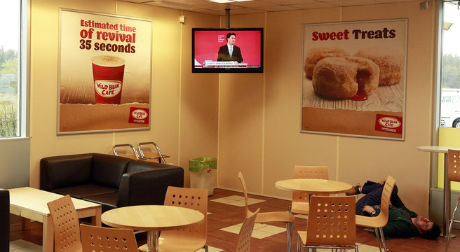 A man stretches on the floor in a service station as Labour leader Ed Miliband is seen giving a speech on the television, near Glasgow