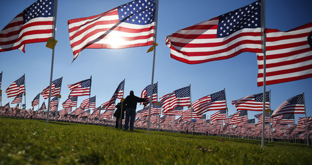 A man has his picture taken by his wife next to a flag in honor of his father during Veterans Day weekend in Aurora