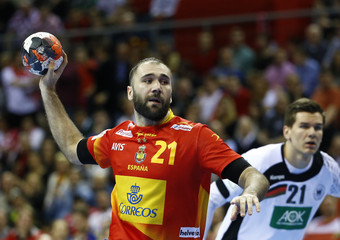 Canellas of Spain shoots past Schmidt of Germany during their Men's European Handball Championship final match in Krakow