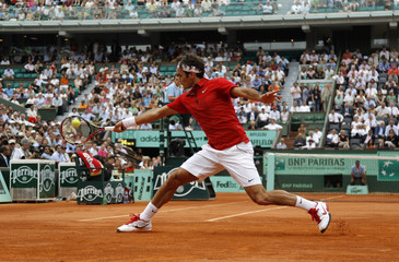 Federer of Switzerland returns the ball to Djokovic of Serbia during their semi-final match at the French Open tennis tournament at the Roland Garros stadium in Paris