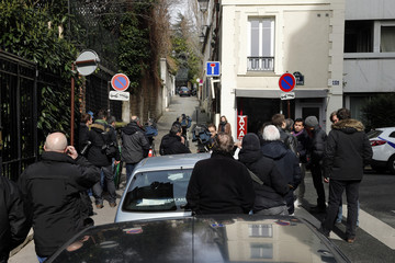 Journalists stand in the street next to former French President Nicolas Sarkozy's residence in Paris