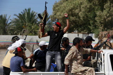 Libyan rebel fighters celebrate as they advance through the town of Maia, 25 kms west of Tripoli