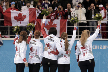 Winners Canada's alternate Wall, first McEwen, second Officer, vice Lawes and skip Jones raise their bouquets to spectators at flower ceremony after their women's gold medal curling game against Sweden during Sochi 2014 Winter Olympics