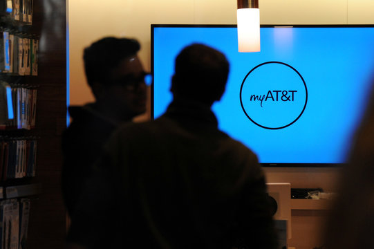Two people talk inside an AT&T store in New York City