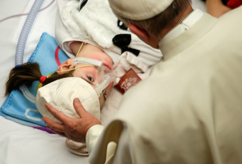 Pope Francis offers his cap to a sick child during a special audience for patients and workers of Bambino Gesu pediatric hospital in Paul VI's hall at the Vatican