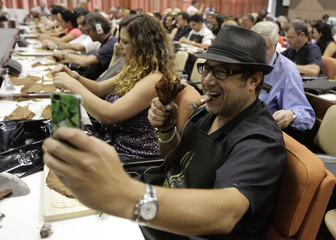 A cigar enthusiast from San Diego, California, takes a picture of his produce at a rolling lesson during the 15th annual Havana Cigar Festival