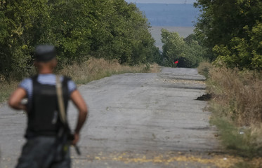 A red flag attached to a pro-Russian separatist tank is seen near a checkpoint of the Ukrainian national guard nearby the town of Slavyanoserbsk
