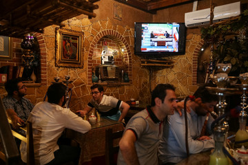Iranians sit in a coffee shop as a TV screen broadcasts election results, in Tehran