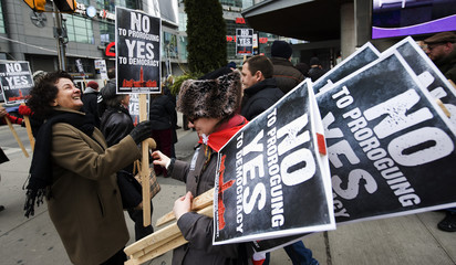 Alex Mandelis hands out signs to protesters during a rally against the federal government's prorogation in Dundas Square in Toronto