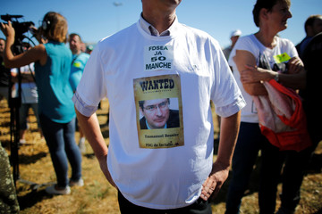 A French dairy farmer from the FNSEA union wears a tee-shirt bearing a picture of Emmanuel Besnier, CEO of Lactalis, during a demonstration to block the round-about access to the Lactalis plant as they protest against the price of milk in Laval