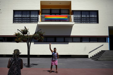 A man flashes the victory sign as he is photographed by a friend in front of a rainbow flag, to mark Gay Pride day, displayed from the Town Hall in Torremolinos