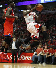 Chicago Bulls' Deng goes to the basket against Philadelphia 76ers' Holiday during the first half of their NBA Eastern Conference quarter-final playoff basketball game in Chicago