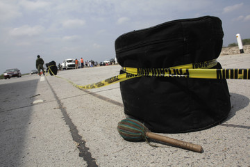 A police cordon tape is tied to a drum at a crash site in Sabinas Hidalgo