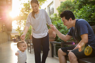 Happy Asian baby with his mother and father playing together in the park