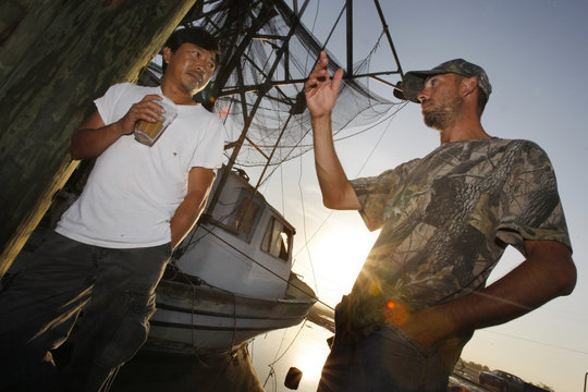 Shrimper Hung Lee and deckhand Matthew Moreau talk in the early morning light at a marina in Buras