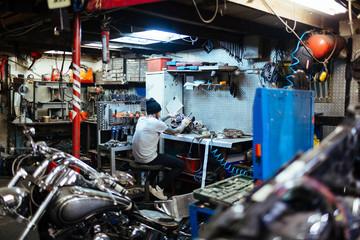 Modern technician repairing carburetor in workshop