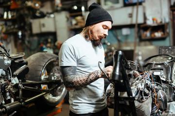 Self-employed repairman working in garage Wall mural