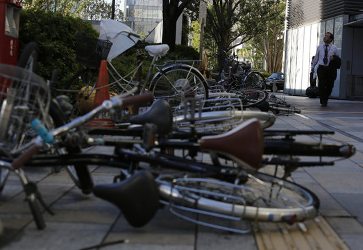 Toppled bicycles lie on a street as a man looks up at the sky while a strong wind caused by tropical storm Vongfong blows in Tokyo