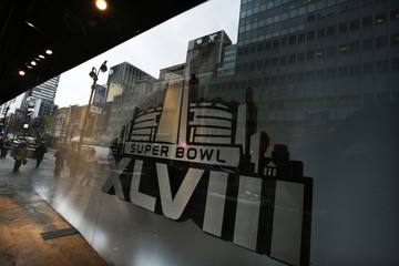 Pedestrians are reflected on windows displaying the Super Bowl icon as preparations continue for Super Bowl XLVIII in New York