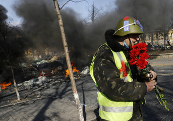 An anti-government protester carries flowers near a burning barricade in Kiev