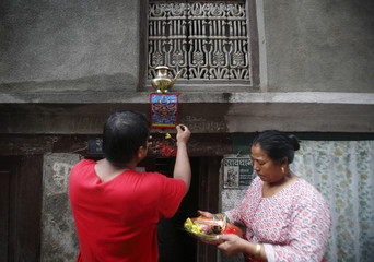 "A man sticks a picture of a snake god at the main entrance of his house, while offering prayers to it to mark the ""Nag Panchami"" festival in Kathmandu"