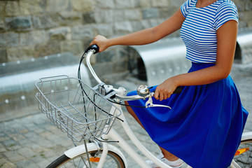 Midsection of young woman riding on bicycle at leisure