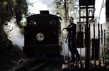Puffing Billy steam railway guard Emma Pallister leans on the levers used to switch tracks as steam engine 12A passes by at Belgrave station near Melbourne