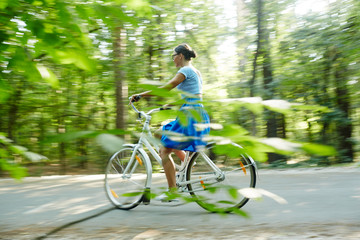 Modern girl riding bicycle down country road
