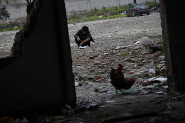 A man injects himself with a syringe at a demolished residential site near the Shanghai Railway Station