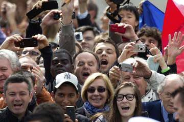 People react as outgoing French President Sarkozy attends a ceremony at the Tomb of the Unknown Soldier at the Arc de Triomphe to commemorte the end of World War II in Paris