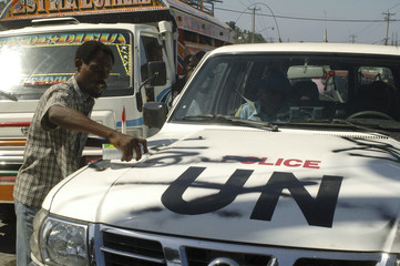 A protester spray paints graffiti on a U.N police car during a demonstration against presidential elections in Port-au-Prince