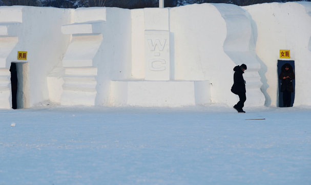 A woman leaves a toilet which has been decorated into a snow sculpture at the Harbin International Snow Sculpture Art Expo in Harbin