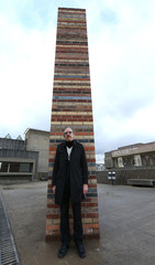 Artist Martin Creed poses for a photograph next to his latest installation, 'Work No 1812: Brick Wall,'  part of the 'What's the point of it ?' exhibition, on the roof of the Hayward Gallery in London